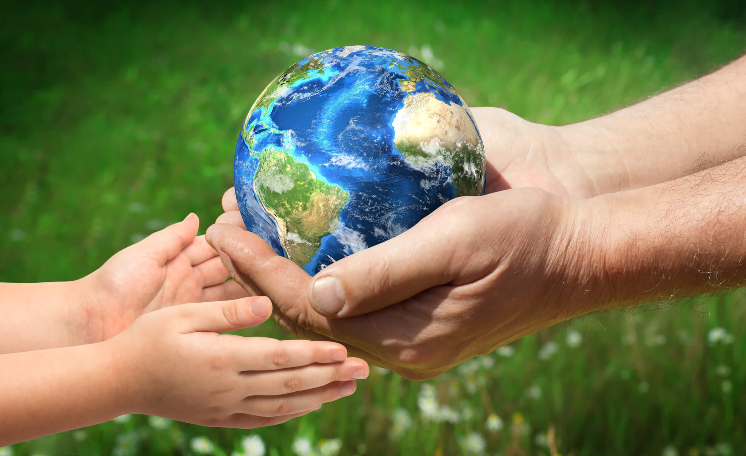 small globe in hands being passed to child